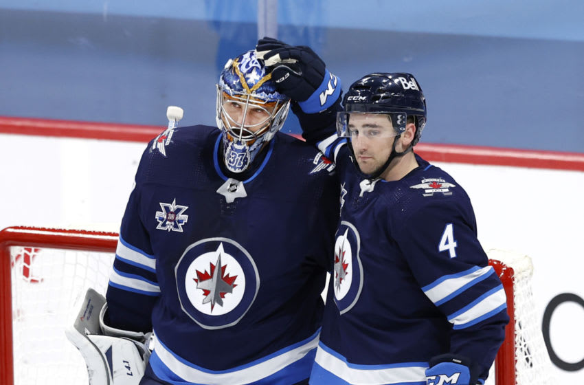 Apr 5, 2021; Winnipeg, Manitoba, CAN; Winnipeg Jets goaltender Connor Hellebuyck (37) and Winnipeg Jets defenseman Neal Pionk (4) celebrate their win over the Ottawa Senators at Bell MTS Place. Mandatory Credit: James Carey Lauder-USA TODAY Sports