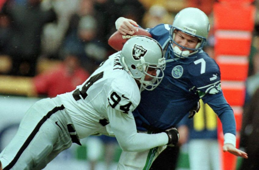 Oakland Raider Tony Bryant (L) sacks Seattle Seahawks' quarterback Jon Kitna (R) during a downpour in the first quarter 16 December 2000 in Seattle, WA. AFP PHOTO/Bill CHAN (Photo by - / AFP) (Photo by -/AFP via Getty Images)