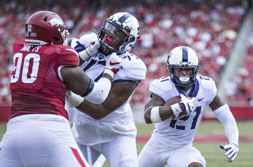 Kyle Hicks #21 runs the ball behind the blocking of Lucas Niang #77 of the TCU Horned Frogs (Photo by Wesley Hitt/Getty Images)