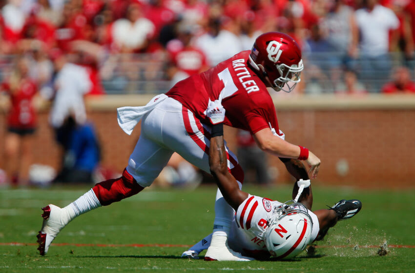 NORMAN, OK - SEPTEMBER 18: Quarterback Spencer Rattler #7 of the Oklahoma Sooners is dragged down by cornerback Quinton Newsome #6 of the Nebraska Cornhuskers in the second quarter at Gaylord Family Oklahoma Memorial Stadium on September 18, 2021 in Norman, Oklahoma. Rattler was called for a facemask on the play. (Photo by Brian Bahr/Getty Images)