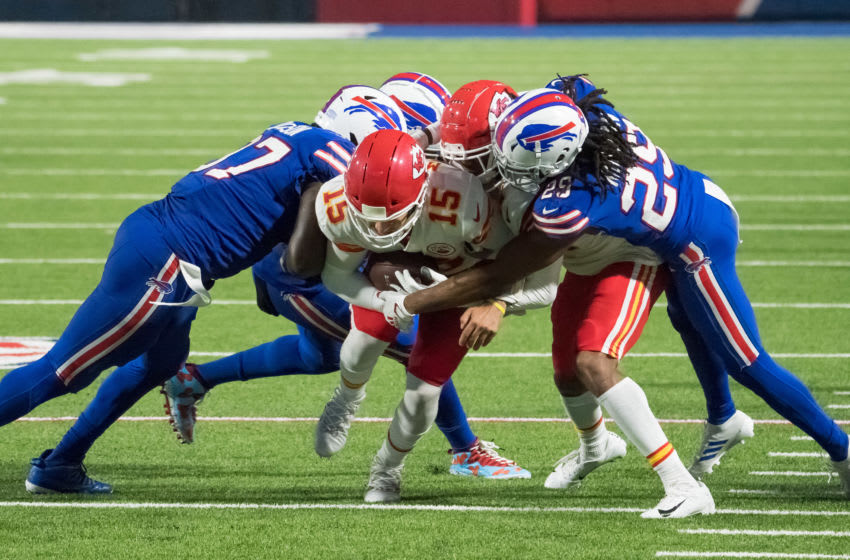 Oct 19, 2020; Orchard Park, New York, USA; Kansas City Chiefs quarterback Patrick Mahomes (15) is tackled by Buffalo Bills cornerback Josh Norman (29) and defensive end Mario Addison (97) after making a first down in the third quarter at Bills Stadium. Mandatory Credit: Mark Konezny-USA TODAY Sports