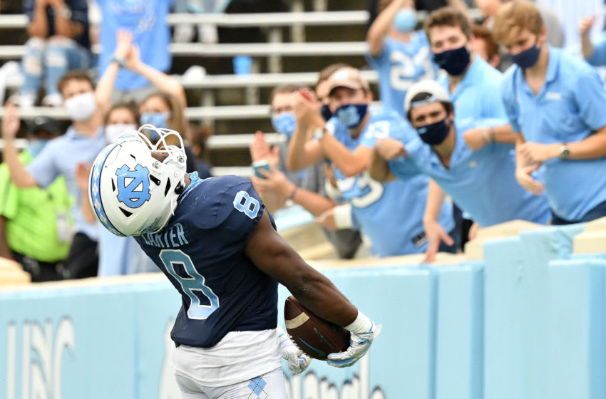CHAPEL HILL, NORTH CAROLINA - OCTOBER 10: Michael Carter #8 of the North Carolina Tar Heels reacts in front of the student section after scoring a touchdown against the Virginia Tech Hokies during their game at Kenan Stadium on October 10, 2020 in Chapel Hill, North Carolina. North Carolina won 56-45. (Photo by Grant Halverson/Getty Images)