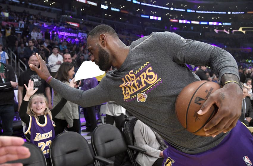 Los Angeles Lakers forward LeBron James high fives a fan before a game. (Photo by Kevork Djansezian/Getty Images)