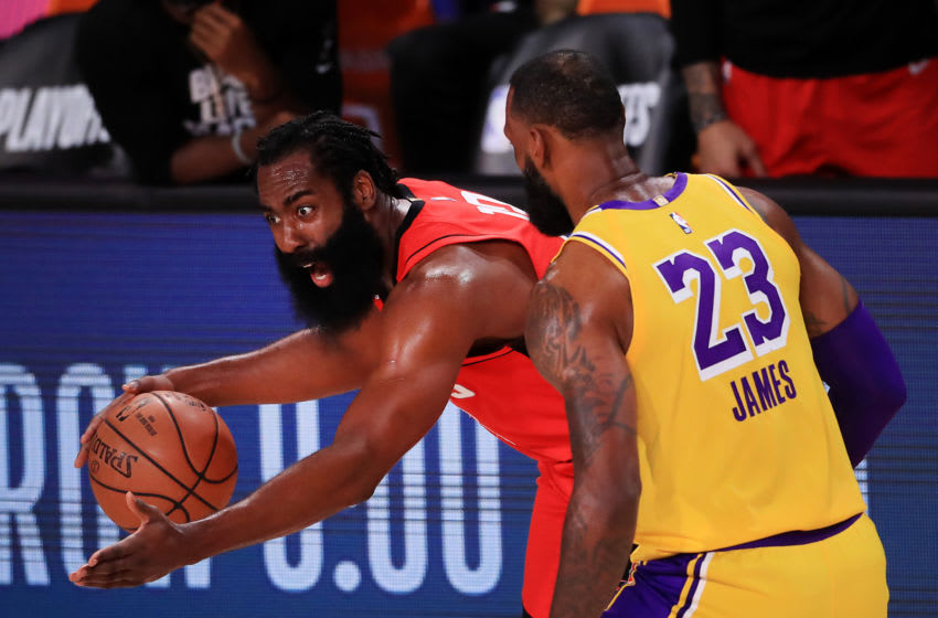 LAKE BUENA VISTA, FLORIDA - SEPTEMBER 10: James Harden #13 of the Houston Rockets drives the ball against LeBron James #23 of the Los Angeles Lakers during the first quarter in Game Four of the Western Conference Second Round during the 2020 NBA Playoffs at AdventHealth Arena at the ESPN Wide World Of Sports Complex on September 10, 2020 in Lake Buena Vista, Florida. NOTE TO USER: User expressly acknowledges and agrees that, by downloading and or using this photograph, User is consenting to the terms and conditions of the Getty Images License Agreement. (Photo by Michael Reaves/Getty Images)