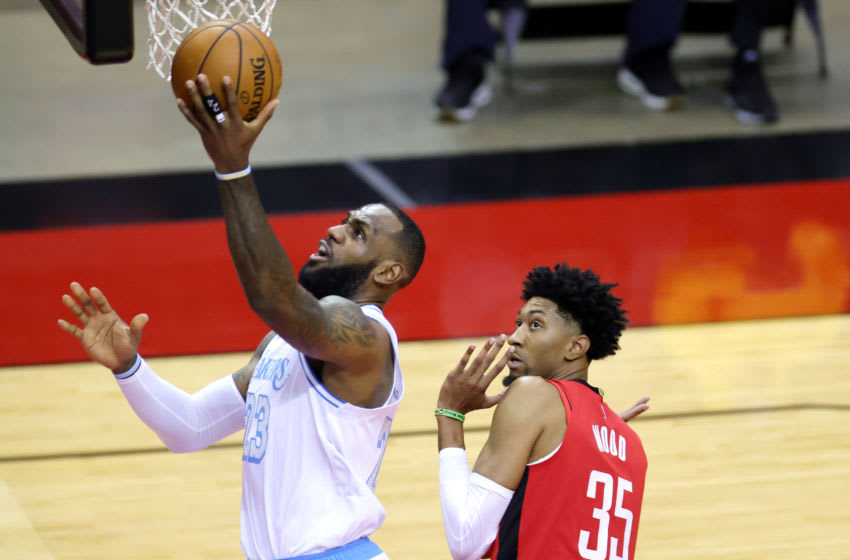 HOUSTON, TEXAS - JANUARY 10: LeBron James #23 of the Los Angeles Lakers goes up for a basket ahead of Christian Wood #35 of the Houston Rockets during the first quarter of a game at Toyota Center on January 10, 2021 in Houston, Texas. NOTE TO USER: User expressly acknowledges and agrees that, by downloading and or using this photograph, User is consenting to the terms and conditions of the Getty Images License Agreement. (Photo by Carmen Mandato/Getty Images)