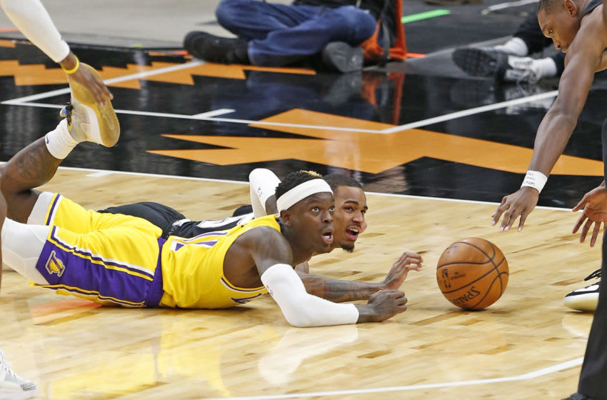 SAN ANTONIO, TX - JANUARY 1: Dejounte Murray #5 of the San Antonio Spurs and Dennis Schroder #17 of the Los Angeles Lakers dive for a loose ball during second half action at AT&T Center on January 1 , 2021 in San Antonio, Texas. NOTE TO USER: User expressly acknowledges and agrees that , by downloading and or using this photograph, User is consenting to the terms and conditions of the Getty Images License Agreement. (Photo by Ronald Cortes/Getty Images)
