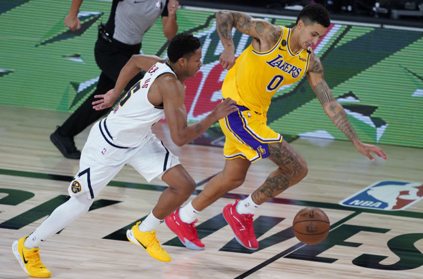 Aug 10, 2020; Lake Buena Vista, Florida, USA; Los Angeles Lakers' Kyle Kuzma (0) tries to outrun Denver Nuggets' PJ Dozier (35) on a drive to the basket during the second half of an NBA basketball game Monday, Aug. 10, 2020, in Lake Buena Vista, Fla. at AdventHealth Arena. Mandatory Credit: Ashley Landis/Pool Photo-USA TODAY Sports