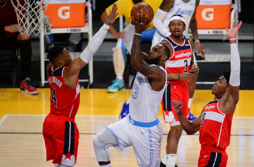 Feb 22, 2021; Los Angeles, California, USA; Los Angeles Lakers forward LeBron James (23) moves to the basket against Washington Wizards guard Russell Westbrook (4) and forward Rui Hachimura (8) during the first half at Staples Center. Mandatory Credit: Gary A. Vasquez-USA TODAY Sports