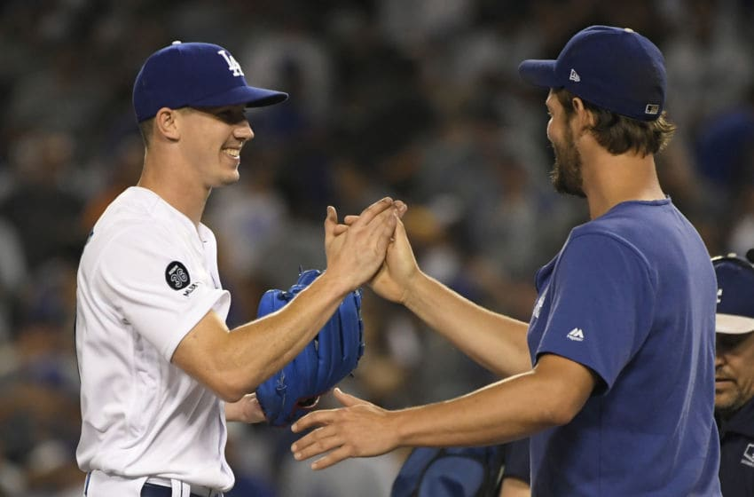LOS ANGELES, CA - AUGUST 03: Walker Buehler #21 of the Los Angeles Dodgers is congratulated by Clayton Kershaw #22 after he pitched a complete game to win over the San Diego Padresat Dodger Stadium on August 3, 2019 in Los Angeles, California. Dodgers won 4-1. (Photo by John McCoy/Getty Images)