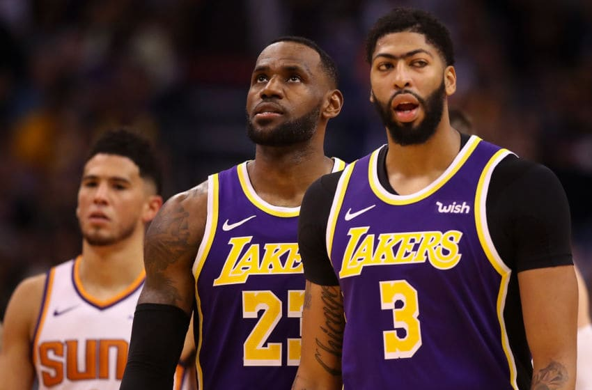 PHOENIX, ARIZONA - NOVEMBER 12: LeBron James #23 of the Los Angeles Lakers stands between Devin Booker #1 of the Phoenix Suns and Anthony Davis #3 during the second half of the NBA game at Talking Stick Resort Arena on November 12, 2019 in Phoenix, Arizona. The Lakers defeated the Suns 123-115. NOTE TO USER: User expressly acknowledges and agrees that, by downloading and/or using this photograph, user is consenting to the terms and conditions of the Getty Images License Agreement (Photo by Christian Petersen/Getty Images)