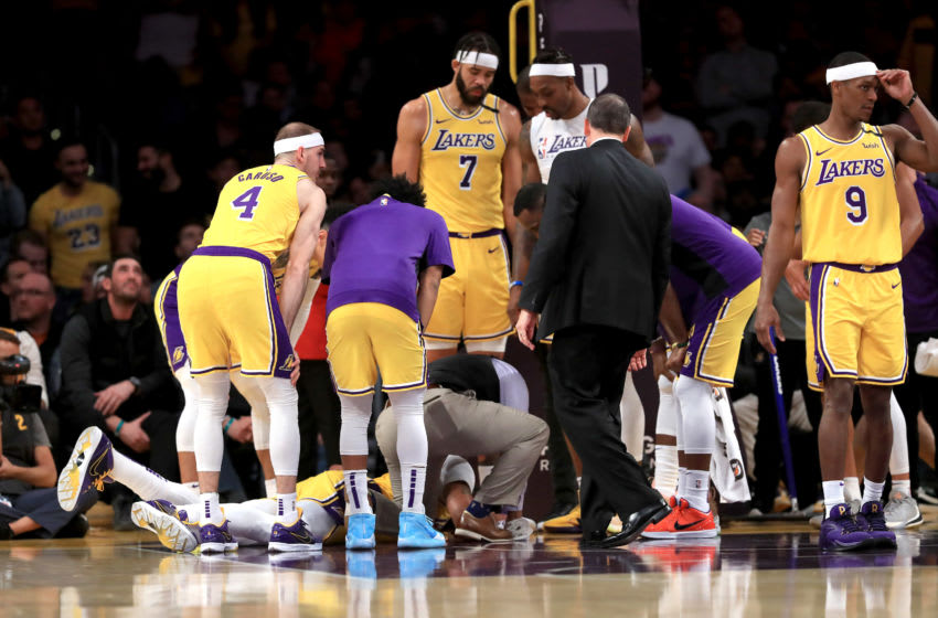 LOS ANGELES, CALIFORNIA - JANUARY 07: Alex Caruso #4, JaVale McGee #7, Rajon Rondo #9 and Dwight Howard #39 look on as Anthony Davis #3 of the Los Angeles Lakers lies on the ground after being injured contesting a shot by Julius Randle #30 of the New York Knicks look on during the second half of a game at Staples Center on January 07, 2020 in Los Angeles, California. NOTE TO USER: User expressly acknowledges and agrees that, by downloading and/or using this photograph, user is consenting to the terms and conditions of the Getty Images License Agreement (Photo by Sean M. Haffey/Getty Images)