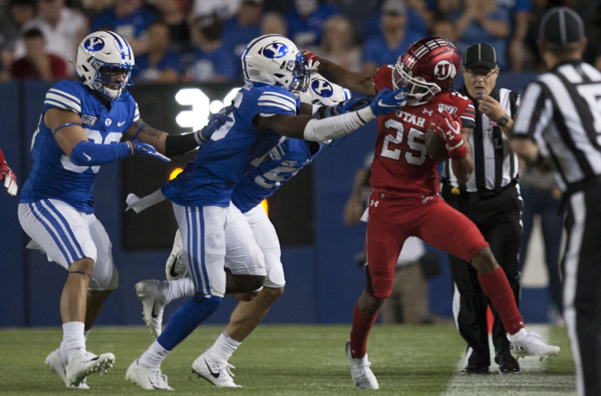 PROVO, UT - AUGUST 29 : Jaylen Dixon #25 of the Utah Utes is face masked as he is taken out of bounds by Mitchell Price #26, Jackson Kaufusi #38 and Dayan Ghanwoloku #5 of the BYU Cougars during their game at LaVell Edwards Stadium on August 29, in Provo, Utah. (Photo by Chris Gardner/Getty Images)