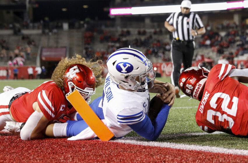 HOUSTON, TEXAS - OCTOBER 16: Zach Wilson #1 of the BYU Cougars is tackled near the goal line by Grant Stuard #0 of the Houston Cougars and Gervarrius Owens #32 in the first half at TDECU Stadium on October 16, 2020 in Houston, Texas. (Photo by Tim Warner/Getty Images)