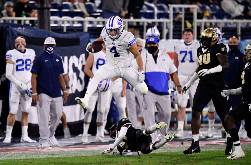 BOCA RATON, FLORIDA - DECEMBER 22: Lopini Katoa #4 of the Brigham Young Cougars leaps over against the Central Florida Knights at FAU Stadium on December 22, 2020 in Boca Raton, Florida. (Photo by Mark Brown/Getty Images)