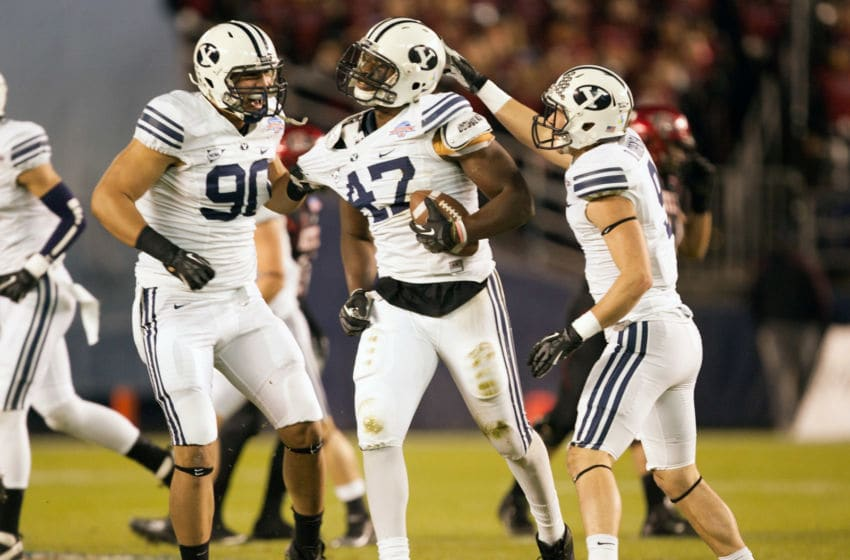 SAN DIEGO, CA - DECEMBER 20: Ezekial Ansah #47 of the BYU Cougars celebrates with teammates Branson Kaufusi #90 and Daniel Sorensen #9 after intercepting the ball in the first half of the game against the San Diego State Aztecs in the Poinsettia Bowl at Qualcomm Stadium on December 20, 2012 in San Diego, California. (Photo by Kent C. Horner/Getty Images)