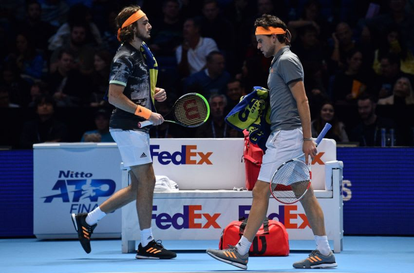 Greece's Stefanos Tsitsipas passes Austria's Dominic Thiem as they swap ends to start the third set during the men's singles final match on day eight of the ATP World Tour Finals tennis tournament at the O2 Arena in London on November 17, 2019. (Photo by Glyn KIRK / AFP) (Photo by GLYN KIRK/AFP via Getty Images)
