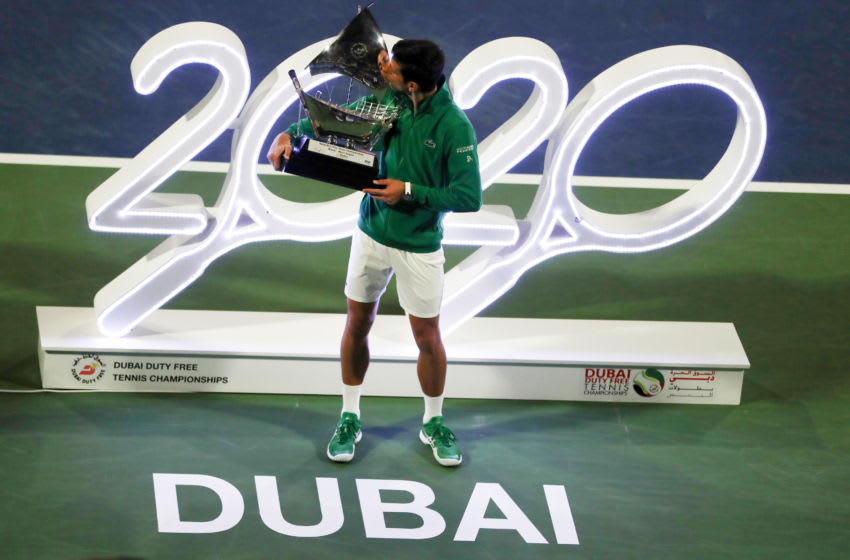 DUBAI, UNITED ARAB EMIRATES - FEBRUARY 29: Novak Djokovic of Serbia celebrates with the victor's trophy after winning the final against Stefanos Tsitsipas of Greece Match Day thirteen of the Dubai Duty Free Tennis at Dubai Duty Free Tennis Stadium on February 29, 2020 in Dubai, United Arab Emirates. (Photo by Amin Mohammad Jamali/Getty Images)