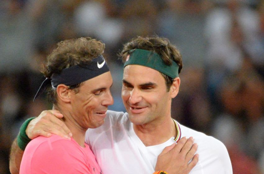 Switzerland's Roger Federer (R) hugs Spain's Rafael Nadal (L) during their tennis match at The Match in Africa at the Cape Town Stadium, in Cape Town on February 7, 2020. (Photo by RODGER BOSCH / AFP) (Photo by RODGER BOSCH/AFP via Getty Images)