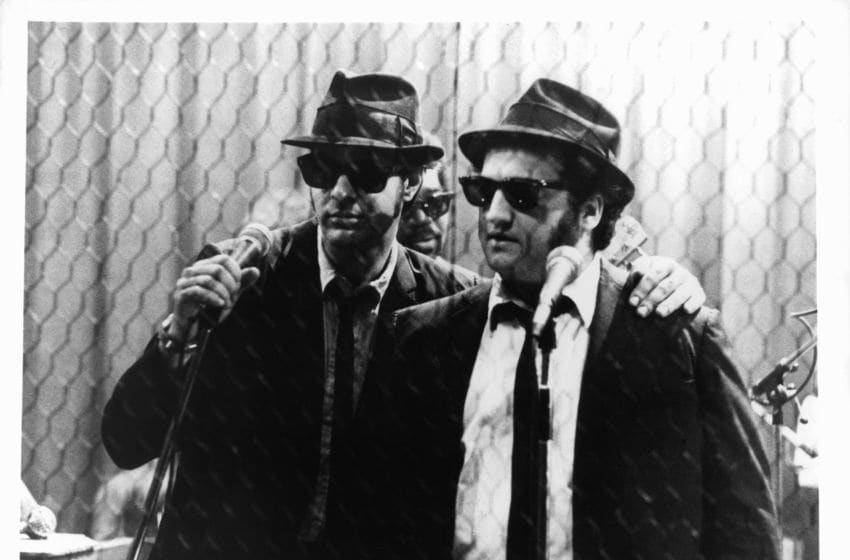 Dan Aykroyd holds a microphone standing next to John Belushi in a scene from the film 'The Blues Brothers', 1980. (Photo by Universal Pictures/Getty Images)