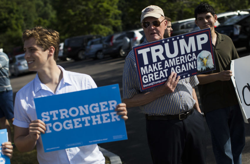 PORTSMOUTH, NH - JULY 12: A supporter of Republican presidential candidate Donald Trump holds up a sign in front of a campaign event with U.S. Senator and former presidential candidate Bernie Sanders and U.S. Presidential candidate Hillary Clinton in Portsmouth, N.H., July 12, 2016. (Photo by Keith Bedford/The Boston Globe via Getty Images)