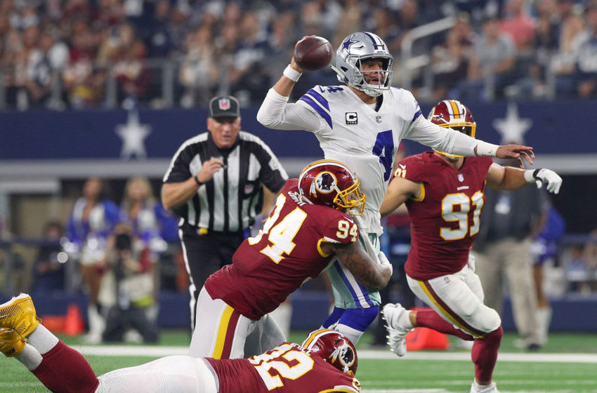 ARLINGTON, TEXAS - NOVEMBER 22: Dak Prescott #4 of the Dallas Cowboys passes the ball as he is tackled by Preston Smith #94 and Stacy McGee #92 of the Washington Redskins in the second quarter at AT&T Stadium on November 22, 2018 in Arlington, Texas. (Photo by Richard Rodriguez/Getty Images)