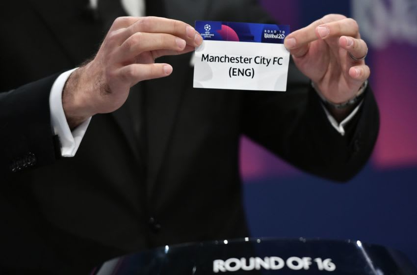 UEFA Champions League's ambassador Hamit Altintop holds the slip of Manchester City during the UEFA Champions League football cup round of 16 draw ceremony on December 16, 2019 in Nyon. (Photo by Fabrice COFFRINI / AFP) (Photo by FABRICE COFFRINI/AFP via Getty Images)