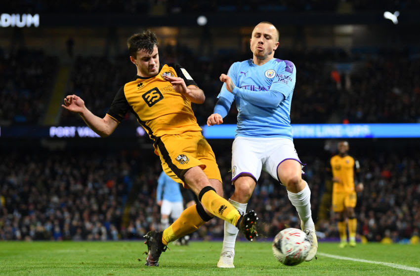 MANCHESTER, ENGLAND - JANUARY 04: Angelino of Manchester City battles for possession with James Gibbons of Port Vale during the FA Cup Third Round match between Manchester City and Port Vale at Etihad Stadium on January 04, 2020 in Manchester, England. (Photo by Clive Mason/Getty Images)
