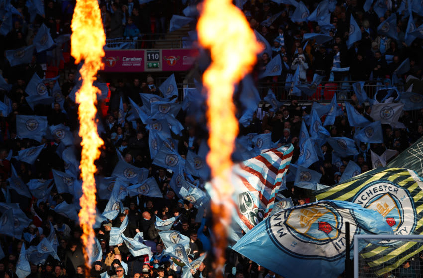 LONDON, ENGLAND - MARCH 01: Pyrotechnics are set off against a backdrop of Manchester City fans waving flags during the Carabao Cup Final between Aston Villa and Manchester City at Wembley Stadium on March 1, 2020 in London, England. (Photo by Marc Atkins/Getty Images)