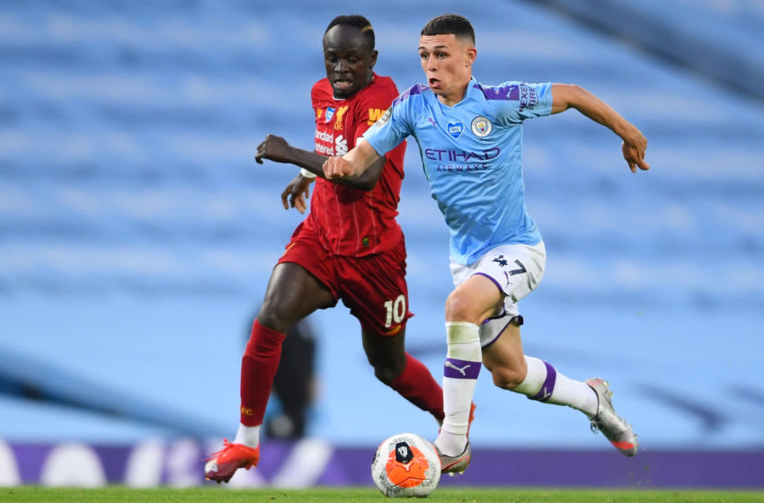Manchester City's English midfielder Phil Foden (R) vies with Liverpool's Senegalese striker Sadio Mane (L) during the English Premier League football match between Manchester City and Liverpool at the Etihad Stadium in Manchester, north west England, on July 2, 2020. (Photo by LAURENCE GRIFFITHS / POOL / AFP) / RESTRICTED TO EDITORIAL USE. No use with unauthorized audio, video, data, fixture lists, club/league logos or 'live' services. Online in-match use limited to 120 images. An additional 40 images may be used in extra time. No video emulation. Social media in-match use limited to 120 images. An additional 40 images may be used in extra time. No use in betting publications, games or single club/league/player publications. / (Photo by LAURENCE GRIFFITHS/POOL/AFP via Getty Images)