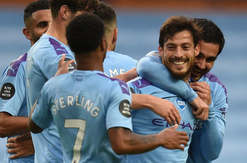 Manchester City's Spanish midfielder David Silva (2R) celebrates scoring their fourth goal during the English Premier League football match between Manchester City and Newcastle United at the Etihad Stadium in Manchester, north west England, on July 8, 2020. (Photo by Oli SCARFF / POOL / AFP) / RESTRICTED TO EDITORIAL USE. No use with unauthorized audio, video, data, fixture lists, club/league logos or 'live' services. Online in-match use limited to 120 images. An additional 40 images may be used in extra time. No video emulation. Social media in-match use limited to 120 images. An additional 40 images may be used in extra time. No use in betting publications, games or single club/league/player publications. / (Photo by OLI SCARFF/POOL/AFP via Getty Images)