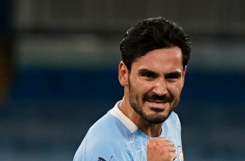 Manchester City's German midfielder Ilkay Gundogan celebrates scoring their second goal from a free kick during the UEFA Champions League football Group C match between Manchester City and Porto at the Etihad Stadium in Manchester, north west England on October 21, 2020. (Photo by Tim Keeton / POOL / AFP) (Photo by TIM KEETON/POOL/AFP via Getty Images)