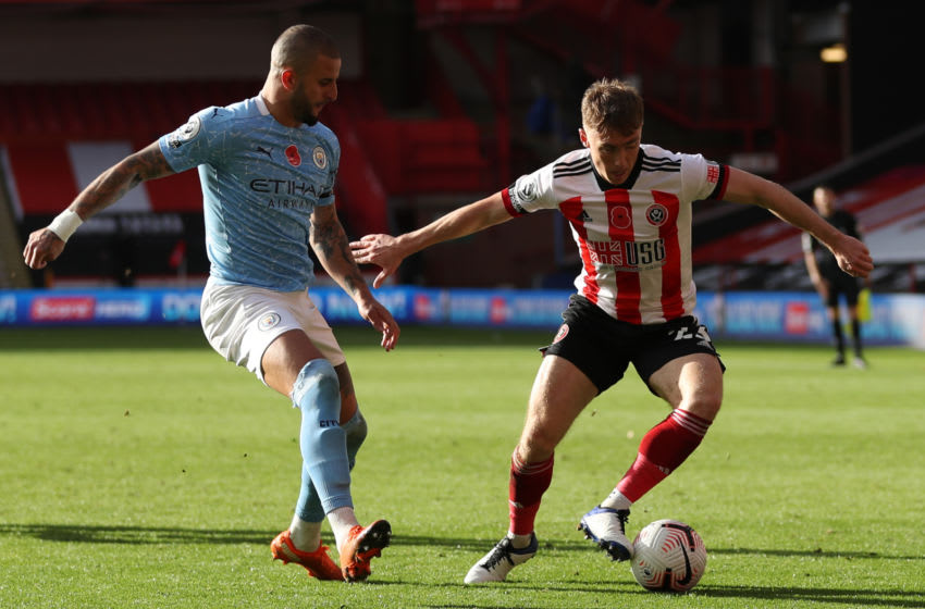 Manchester City's English defender Kyle Walker (L) vies with Sheffield United's English midfielder Ben Osborn during the English Premier League football match between Sheffield United and Manchester City at Bramall Lane in Sheffield, northern England on October 31, 2020. (Photo by Catherine Ivill / POOL / AFP) / RESTRICTED TO EDITORIAL USE. No use with unauthorized audio, video, data, fixture lists, club/league logos or 'live' services. Online in-match use limited to 120 images. An additional 40 images may be used in extra time. No video emulation. Social media in-match use limited to 120 images. An additional 40 images may be used in extra time. No use in betting publications, games or single club/league/player publications. / (Photo by CATHERINE IVILL/POOL/AFP via Getty Images)