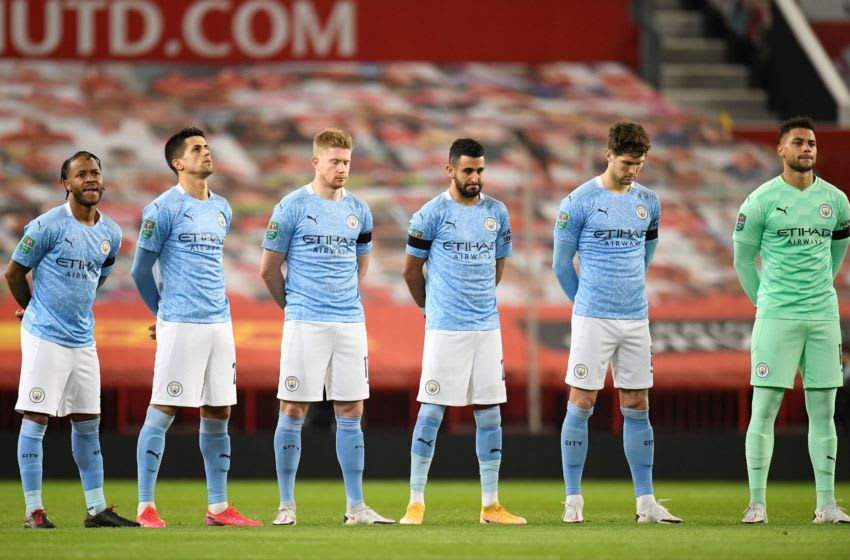 Manchester City players stand during a minute's silence in memory of English footballer Colin Bell who passed away yesterday the English League Cup semi final first leg football match between Manchester United and Manchester City at Old Trafford in Manchester, north west England, on January 6, 2021. (Photo by PETER POWELL / POOL / AFP) / RESTRICTED TO EDITORIAL USE. No use with unauthorized audio, video, data, fixture lists, club/league logos or 'live' services. Online in-match use limited to 120 images. An additional 40 images may be used in extra time. No video emulation. Social media in-match use limited to 120 images. An additional 40 images may be used in extra time. No use in betting publications, games or single club/league/player publications. / (Photo by PETER POWELL/POOL/AFP via Getty Images)