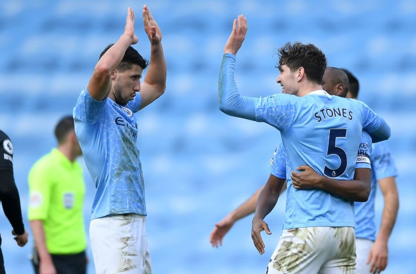 Manchester City's Portuguese defender Ruben Dias (L) celebrates with Manchester City's English defender John Stones after the final whistle during the English Premier League football match between Manchester City and West Ham United at the Etihad Stadium in Manchester, north west England, on February 27, 2021. - Manchester City won the match 2-0. (Photo by Gareth Copley / POOL / AFP) / RESTRICTED TO EDITORIAL USE. No use with unauthorized audio, video, data, fixture lists, club/league logos or 'live' services. Online in-match use limited to 120 images. An additional 40 images may be used in extra time. No video emulation. Social media in-match use limited to 120 images. An additional 40 images may be used in extra time. No use in betting publications, games or single club/league/player publications. / (Photo by GARETH COPLEY/POOL/AFP via Getty Images)