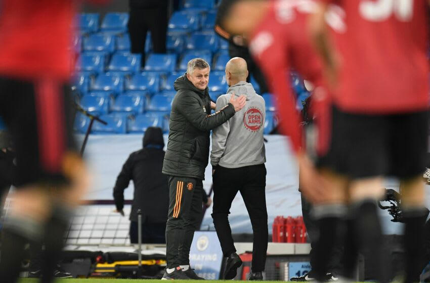 Manchester United's Norwegian manager Ole Gunnar Solskjaer (L) and Manchester City's Spanish manager Pep Guardiola (R) interact after the final whistle of the English Premier League football match between Manchester City and Manchester United at the Etihad Stadium in Manchester, north west England, on March 7, 2021. (Photo by PETER POWELL / POOL / AFP) / RESTRICTED TO EDITORIAL USE. No use with unauthorized audio, video, data, fixture lists, club/league logos or 'live' services. Online in-match use limited to 120 images. An additional 40 images may be used in extra time. No video emulation. Social media in-match use limited to 120 images. An additional 40 images may be used in extra time. No use in betting publications, games or single club/league/player publications. / (Photo by PETER POWELL/POOL/AFP via Getty Images)