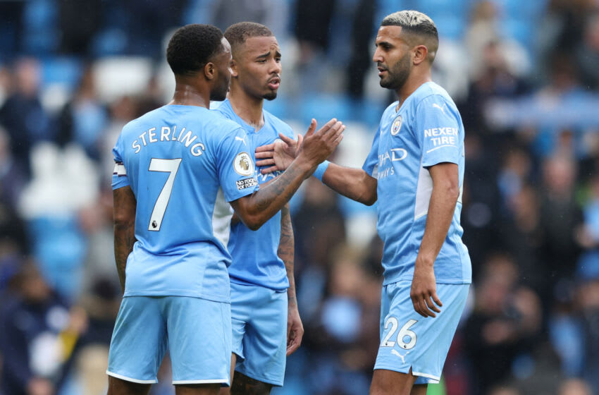 Manchester City's English midfielder Raheem Sterling (L), Manchester City's Brazilian striker Gabriel Jesus (C) and Manchester City's Algerian midfielder Riyad Mahrez (R) celebrate on the pitch after the English Premier League football match between Manchester City and Norwich City at the Etihad Stadium in Manchester, north west England, on August 21, 2021. - Manchester City won the game 5-0. - RESTRICTED TO EDITORIAL USE. No use with unauthorized audio, video, data, fixture lists, club/league logos or 'live' services. Online in-match use limited to 120 images. An additional 40 images may be used in extra time. No video emulation. Social media in-match use limited to 120 images. An additional 40 images may be used in extra time. No use in betting publications, games or single club/league/player publications. (Photo by Adrian DENNIS / AFP) / RESTRICTED TO EDITORIAL USE. No use with unauthorized audio, video, data, fixture lists, club/league logos or 'live' services. Online in-match use limited to 120 images. An additional 40 images may be used in extra time. No video emulation. Social media in-match use limited to 120 images. An additional 40 images may be used in extra time. No use in betting publications, games or single club/league/player publications. / RESTRICTED TO EDITORIAL USE. No use with unauthorized audio, video, data, fixture lists, club/league logos or 'live' services. Online in-match use limited to 120 images. An additional 40 images may be used in extra time. No video emulation. Social media in-match use limited to 120 images. An additional 40 images may be used in extra time. No use in betting publications, games or single club/league/player publications. (Photo by ADRIAN DENNIS/AFP via Getty Images)