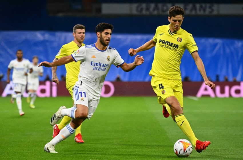 Real Madrid's Spanish midfielder Marco Asensio (L) challenges Villarreal's Spanish defender Pau Torres during the Spanish League football match between Real Madrid and Villarreal CF at the Santiago Bernabeu stadium in Madrid on September 25, 2021. (Photo by GABRIEL BOUYS / AFP) (Photo by GABRIEL BOUYS/AFP via Getty Images)