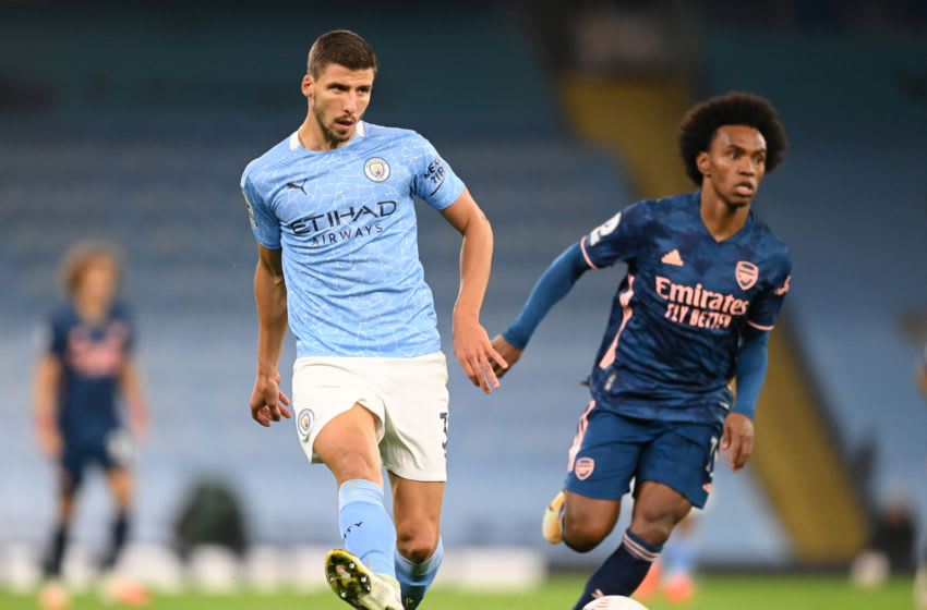 MANCHESTER, ENGLAND - OCTOBER 17: Ruben Dias of Manchester City passes the ball under pressure from Willian of Arsenal during the Premier League match between Manchester City and Arsenal at Etihad Stadium on October 17, 2020 in Manchester, England. Sporting stadiums around the UK remain under strict restrictions due to the Coronavirus Pandemic as Government social distancing laws prohibit fans inside venues resulting in games being played behind closed doors. (Photo by Michael Regan/Getty Images)