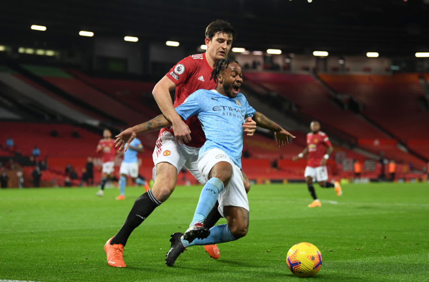MANCHESTER, ENGLAND - DECEMBER 12: Raheem Sterling of Manchester City and Harry Maguire of Manchester United battle for the ball during the Premier League match between Manchester United and Manchester City at Old Trafford on December 12, 2020 in Manchester, England. The match will be played without fans, behind closed doors as a Covid-19 precaution. (Photo by Michael Regan/Getty Images)