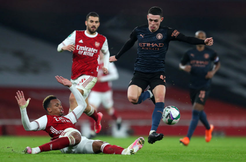 LONDON, ENGLAND - DECEMBER 22: Phil Foden of Manchester City is challenged by Gabriel of Arsenal during the Carabao Cup Quarter Final match between Arsenal and Manchester City at Emirates Stadium on December 22, 2020 in London, England. The match will be played without fans, behind closed doors as a Covid-19 precaution. (Photo by Catherine Ivill/Getty Images)