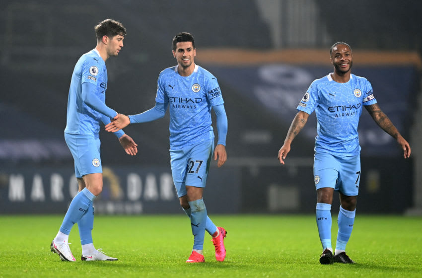 WEST BROMWICH, ENGLAND - JANUARY 26: Joao Cancelo of Manchester City celebrates with team mates John Stones (L) and Raheem Sterling (R) after scoring their team's second goal during the Premier League match between West Bromwich Albion and Manchester City at The Hawthorns on January 26, 2021 in West Bromwich, England. Sporting stadiums around the UK remain under strict restrictions due to the Coronavirus Pandemic as Government social distancing laws prohibit fans inside venues resulting in games being played behind closed doors. (Photo by Michael Regan/Getty Images)