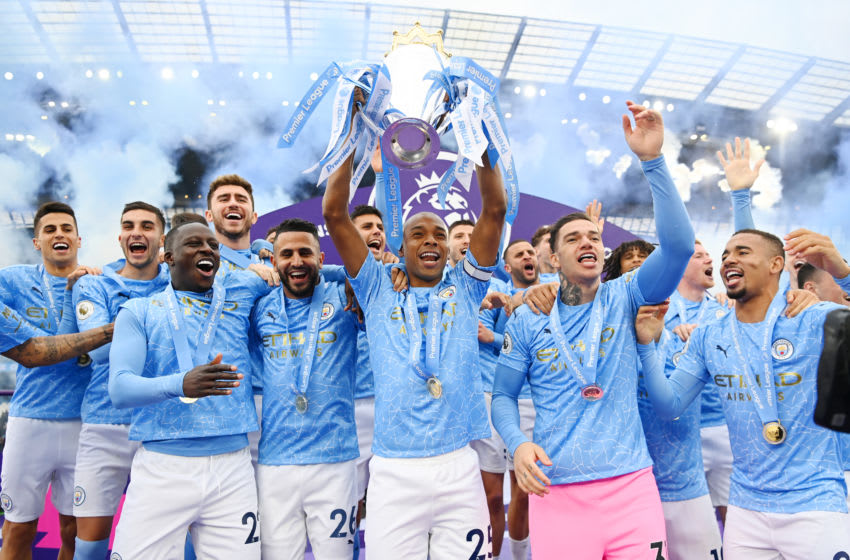 MANCHESTER, ENGLAND - MAY 23: Fernandinho of Manchester City lifts the Premier League Trophy with team mates Benjamin Mendy, Riyad Mahrez, Ederson and Sergio Aguero as Manchester City are presented with the Trophy as they win the league following the Premier League match between Manchester City and Everton at Etihad Stadium on May 23, 2021 in Manchester, England. A limited number of fans will be allowed into Premier League stadiums as Coronavirus restrictions begin to ease in the UK. (Photo by Michael Regan/Getty Images)