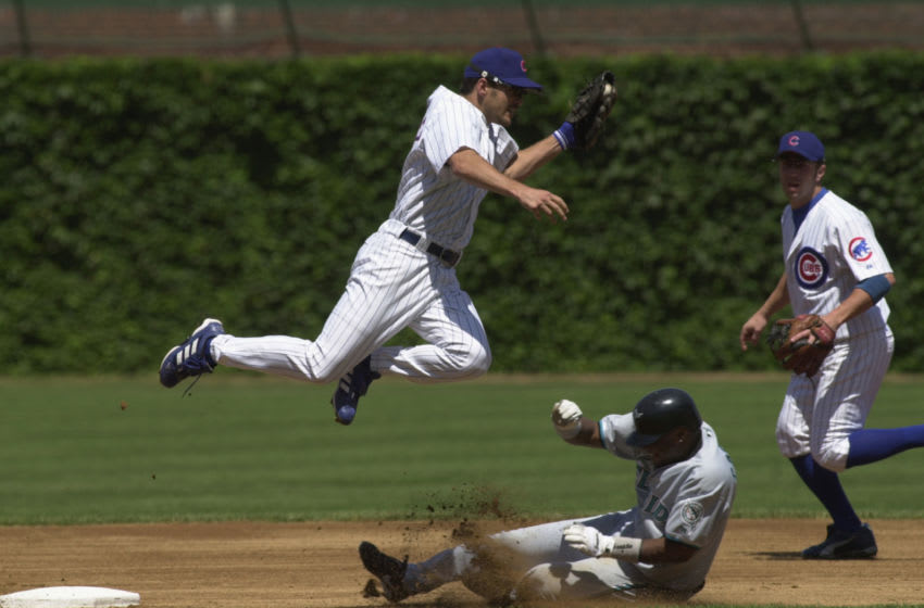 CHICAGO - JULY 12: Second Baseman Mark Belhorn #28 of the Chicago Cubs leaps over sliding second baseman Luis Castillo #1 of the Florida Marlins as he gloves the ball during the game on July 12, 2002 at Wrigley Field in Chicago, Illinois. The Cubs defeated the Marlins 5-4 in 16 innings. (Photo by Jonathan Daniel/Getty Images)