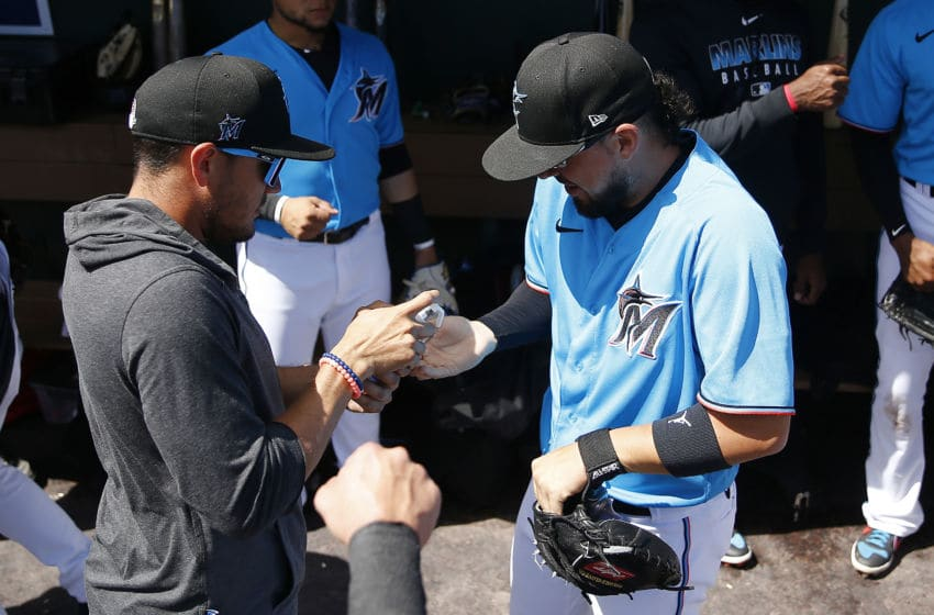 JUPITER, FLORIDA - MARCH 11: Miguel Rojas #19 of the Miami Marlins gives a teammate hand sanitizer after shaking his hand prior to a Grapefruit League spring training against the New York Yankees at Roger Dean Stadium on March 11, 2020 in Jupiter, Florida. (Photo by Michael Reaves/Getty Images)