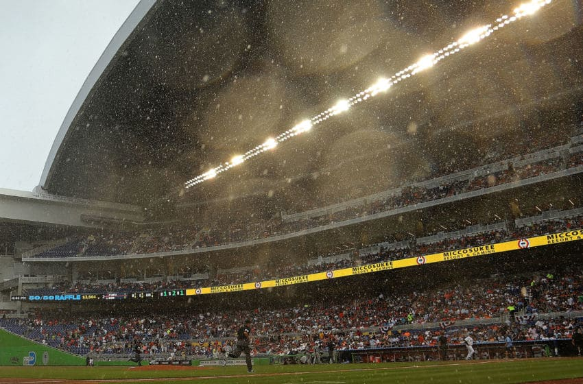 MIAMI, FL - APRIL 06: Teams retreat to the dugout during a rain delay at Marlins Park during Opening Day between the Miami Marlins and the Atlanta Braves on April 6, 2015 in Miami, Florida. (Photo by Mike Ehrmann/Getty Images)