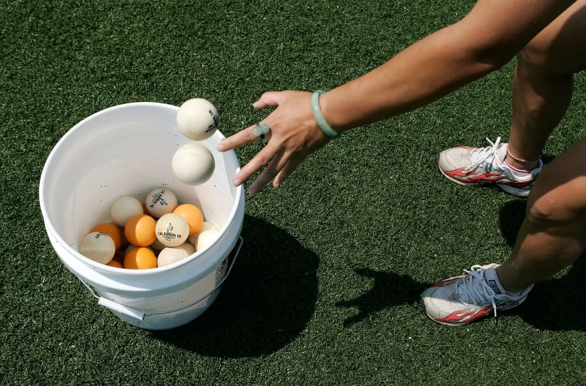 ABERDEEN, MD - AUGUST 14: Chinese softball coach Zhang Xinyan of Shanghai collects balls as Zhang participates in a coaching education program at Ripken Baseball Academy August 14, 2007 in Aberdeen, Maryland. Twelve Chinese baseball and softball coaches took part in a five-week program to learn coaching skills from baseball hall of famer Cal Ripken Jr., who has been named as a special sports envoy of the U.S. State Department, and other Major League Baseball players. The coaches will use what they have learned about baseball in the U.S. to teach young players in their home country. (Photo by Alex Wong/Getty Images)