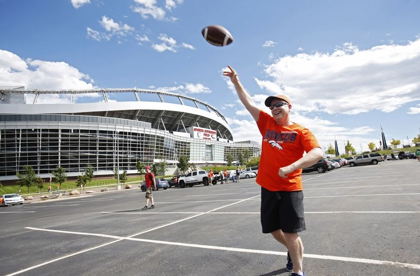 Sep 7, 2014; Denver, CO, USA; Fan Greg Ahern tosses a football at a tailgate party outside the stadium before the game between the Denver Broncos and the Indianapolis Colts at Sports Authority Field at Mile High. Mandatory Credit: Chris Humphreys-USA TODAY Sports