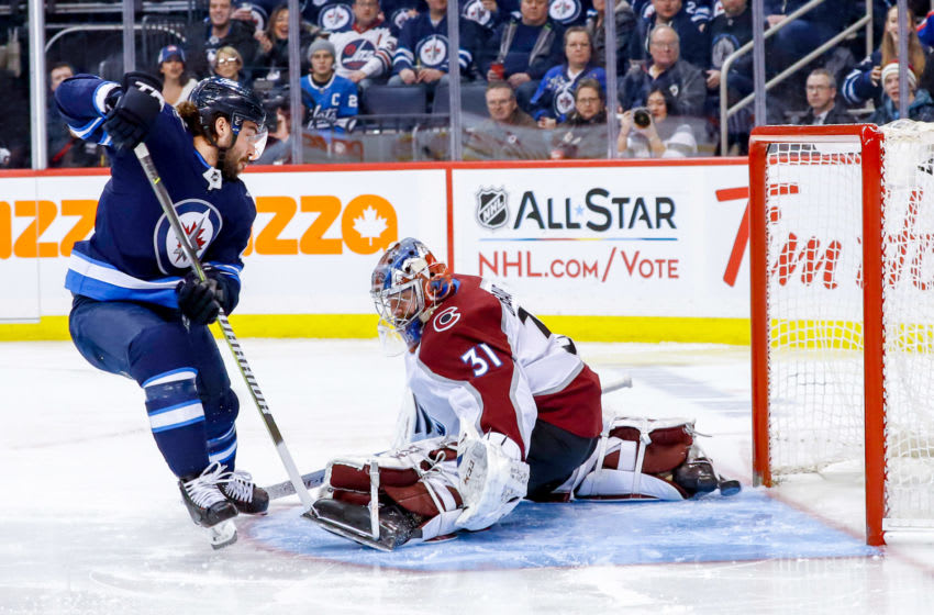 WINNIPEG, MB - JANUARY 8: Mathieu Perreault #85 of the Winnipeg Jets slips the puck underneath goaltender Philipp Grubauer #31 of the Colorado Avalanche for a first period goal at the Bell MTS Place on January 8, 2019 in Winnipeg, Manitoba, Canada. (Photo by Darcy Finley/NHLI via Getty Images)
