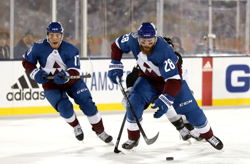 COLORADO SPRINGS, COLORADO - FEBRUARY 15: Ian Cole #28 of the Colorado Avalanche advances the puck against Trevor Moore #12 of the Los Angeles Kings in the third period during the 2020 NHL Stadium Series game at Falcon Stadium on February 15, 2020 in Colorado Springs, Colorado. (Photo by Matthew Stockman/Getty Images)