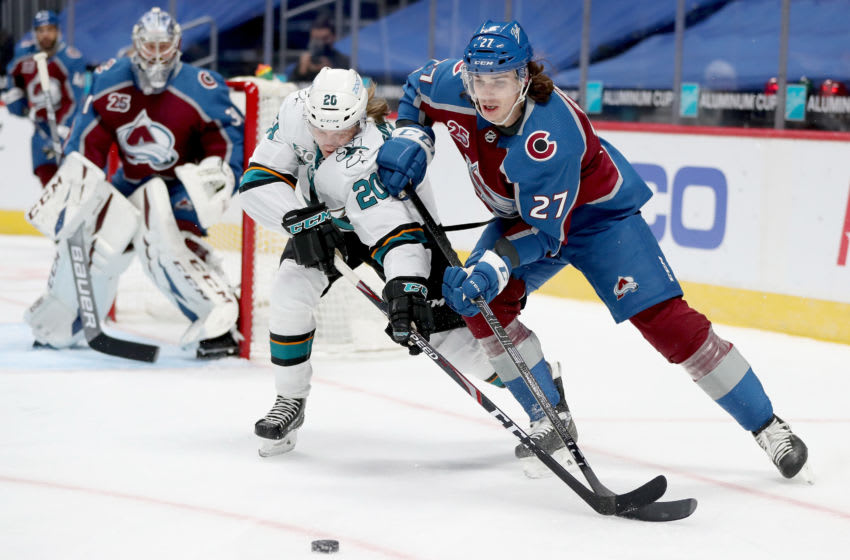 DENVER, COLORADO - JANUARY 26: Ryan Graves #27 of the Colorado Avalanche fights for the puck against Marcus Sorensen #20 of the San Jose Sharks in the first period at Ball Arena on January 26, 2021 in Denver, Colorado. (Photo by Matthew Stockman/Getty Images)